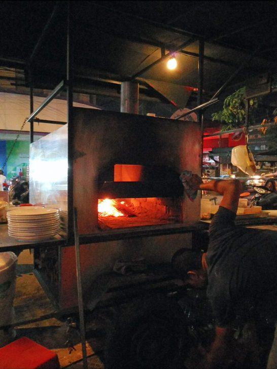 薪?の火でピザを焼き上げる