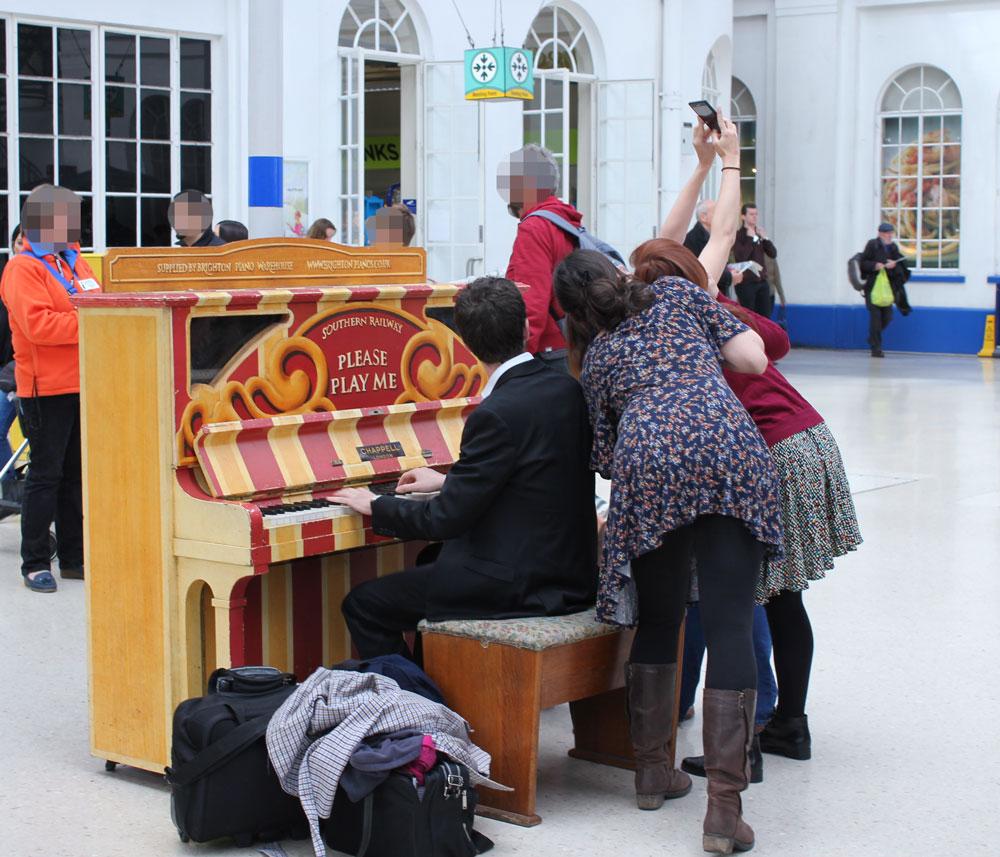 ブライトンの駅でピアノを演奏する男性