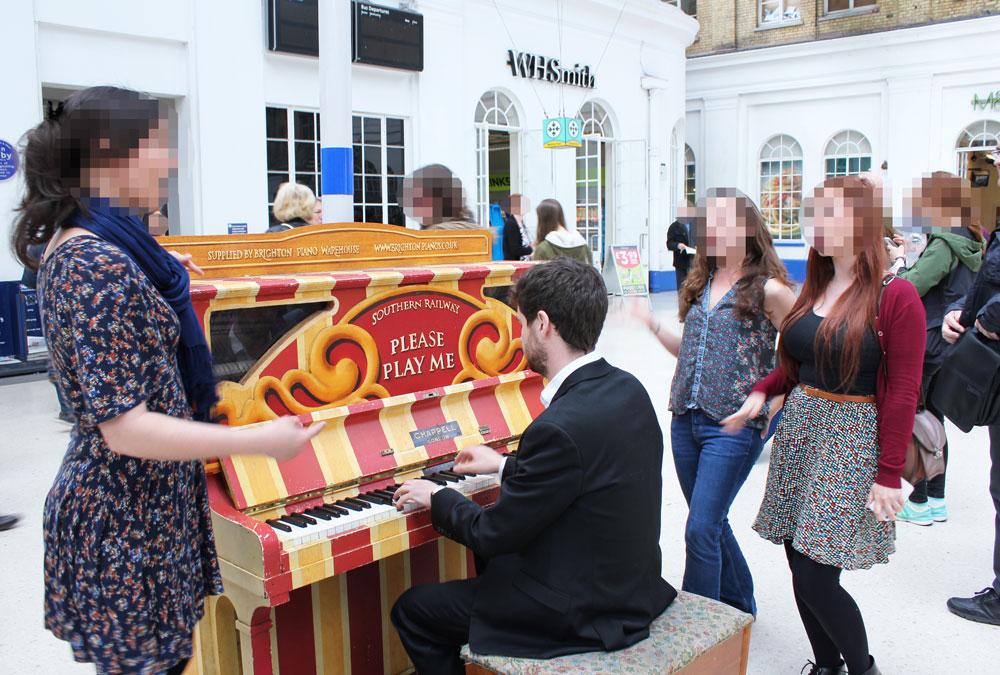ピアノに合わせて歌って踊る女性たち