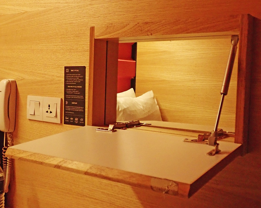 カプセルホテルの客室内にある簡単なデスクと鏡