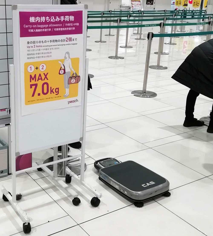 保安検査場入口で機内持ち込み荷物の重さをチェックされる