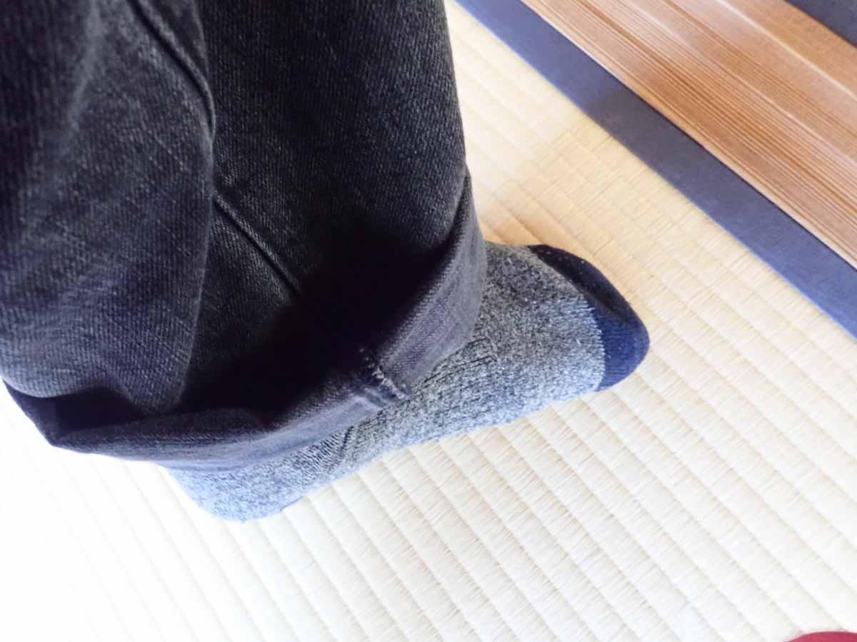 畳を傷つけないようにズボンのすそを上げる